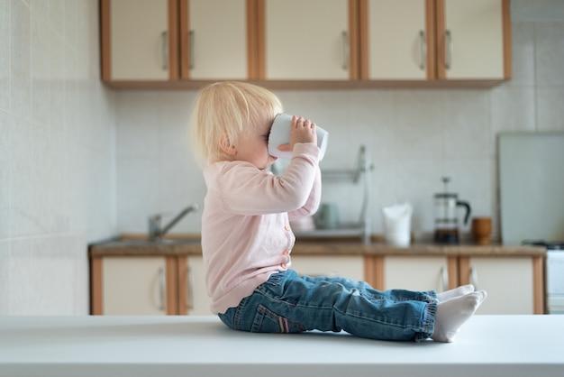 Blonde peuter zit in de keuken en drinkt uit een grote beker. ontbijt thuis.