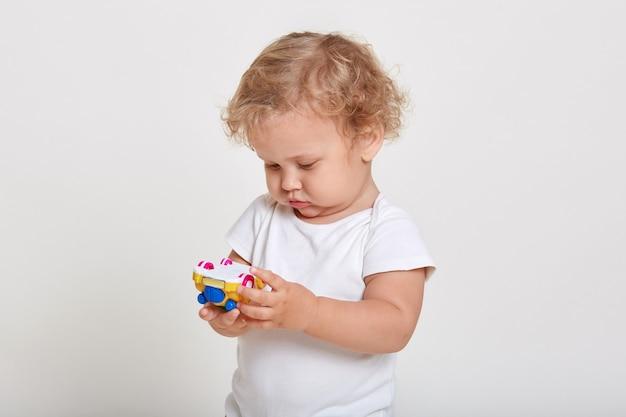 Blonde peuters spelen met kleur auto geïsoleerd op witte ruimte, geconcentreerd speelgoed in zijn handen kijken