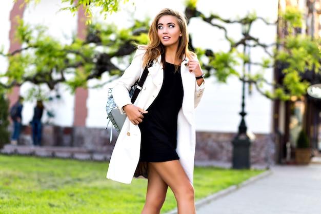 Blonde prachtige vrouw die alleen loopt in het centrum van de stad, een casual elegante jas en jurk draagt, alleen winkelen, streetstyle-mode maakt.