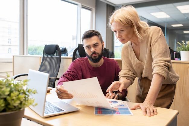 Blonde rijpe onderneemster in vrijetijdskleding die op financieel document richt dat door haar jonge mannelijke collega wordt gehouden terwijl beide de gegevens bespreken