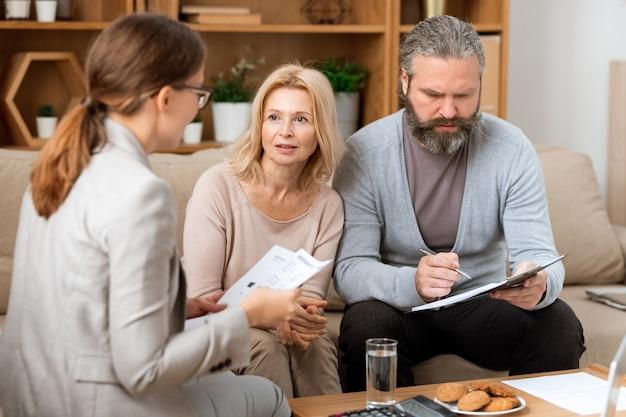 Blonde rijpe vrouw die met makelaar in onroerend goed overlegt terwijl haar echtgenoot document leest alvorens te ondertekenen
