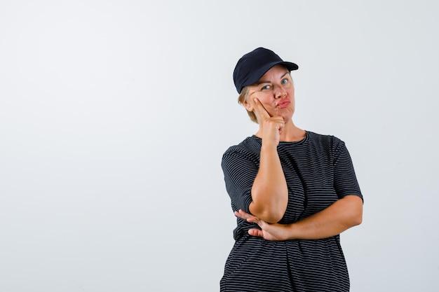 Blonde rijpe vrouw in een zwart t-shirt en een zwarte pet