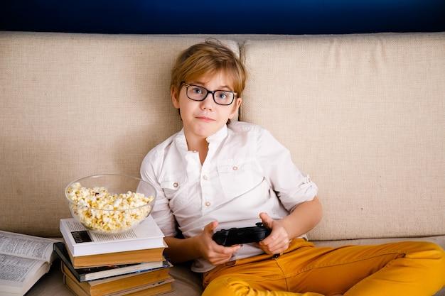 Blonde schooljongen jongen met bril speelt videogames houdt een gamepad eet popcorn