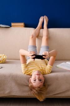 Blonde schooljongen speelt videogames houdt een gamepad vast en eet popcorn in plaats van lessen te leren