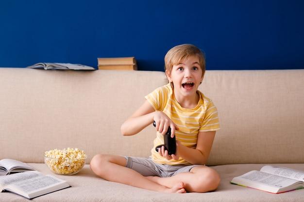Blonde schooljongen speelt videogames houdt een gamepad vast en eet popcorn
