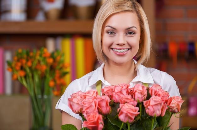 Blonde schoonheid met bos rozen. aantrekkelijke jonge blonde haarvrouw in schort die een bos rozen vasthoudt en glimlacht