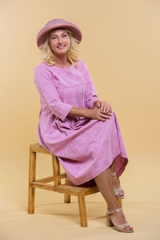 Blonde senior vrouw die zich voordeed op een houten stoel