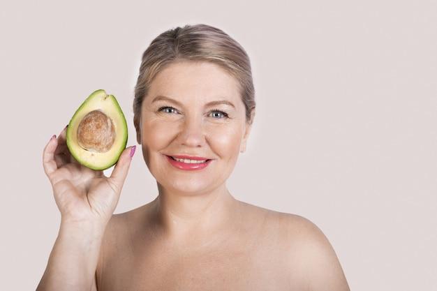 Blonde senior vrouw met blote schouders in evenwicht met een avocado op studiomuur met vrije ruimte en glimlach