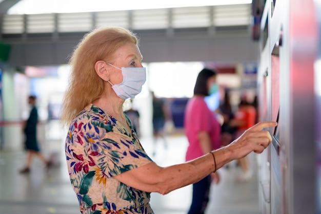 Blonde senior vrouw met masker kaartje kopen bij het sky train station