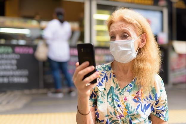 Blonde senior vrouw met masker met behulp van telefoon in de coffeeshop buitenshuis