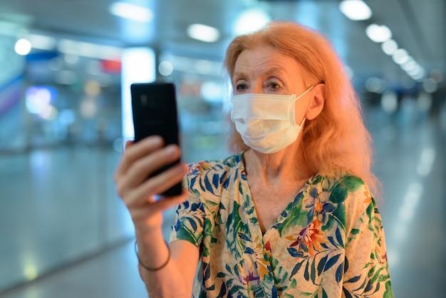 Blonde senior vrouw met masker met behulp van telefoon terwijl sociale afstand nemen bij metrostation