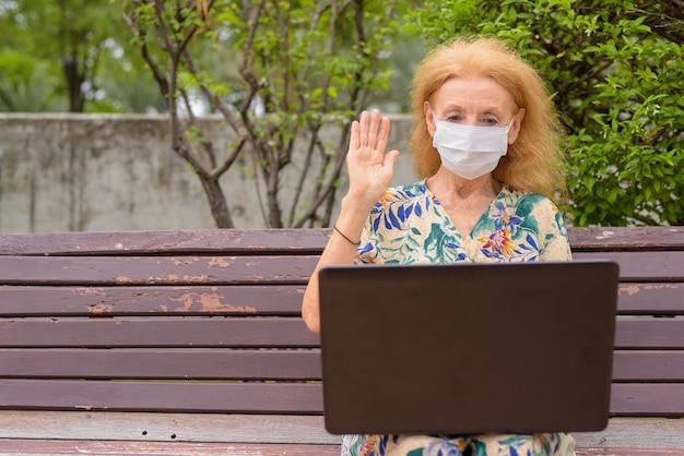Blonde senior vrouw met masker videobellen met behulp van laptop zittend met afstand op een bankje