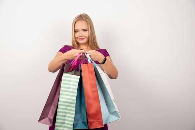 Blonde shopaholic die een stel kleurrijke boodschappentassen vasthoudt.