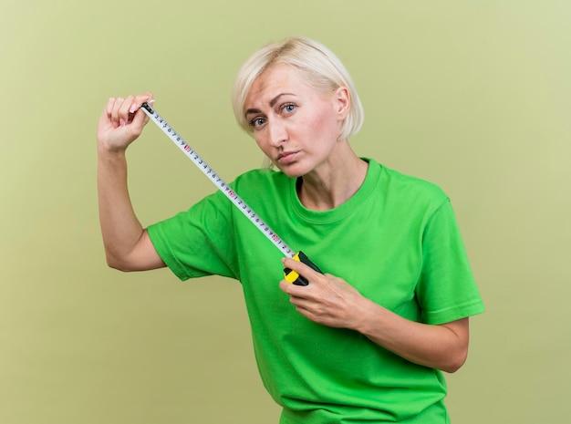 Blonde slavische vrouw die op middelbare leeftijd de meter van de voorholding band bekijkt die op olijfgroene muur wordt geïsoleerd