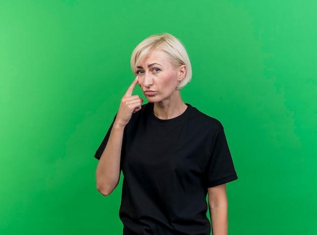 Blonde slavische vrouw op middelbare leeftijd die voorzijde bekijkt die vinger onder oog zet die op groene muur met exemplaarruimte wordt geïsoleerd