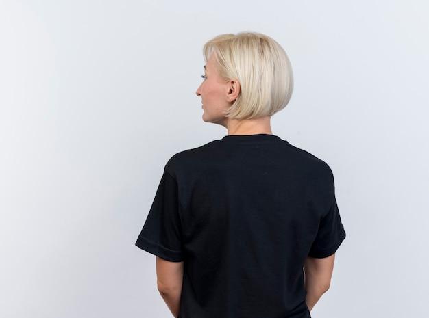 Blonde slavische vrouw op middelbare leeftijd die zich binnen achter mening bevindt die kant bekijkt die op witte achtergrond met exemplaarruimte wordt geïsoleerd