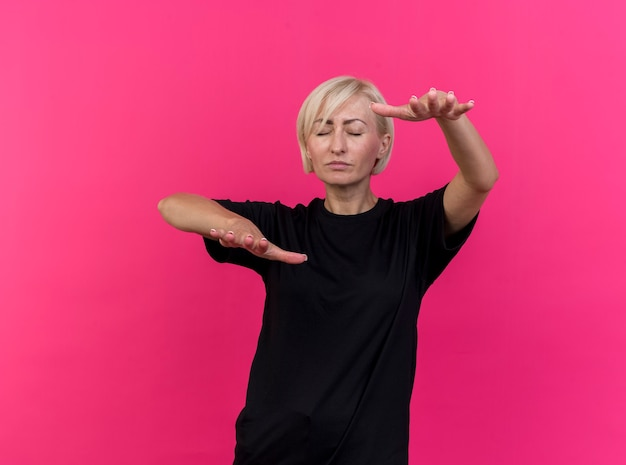 Blonde slavische vrouw van middelbare leeftijd die met gesloten ogen loopt die uit handen naar camera uitrekt die op karmozijnrode achtergrond met exemplaarruimte wordt geïsoleerd