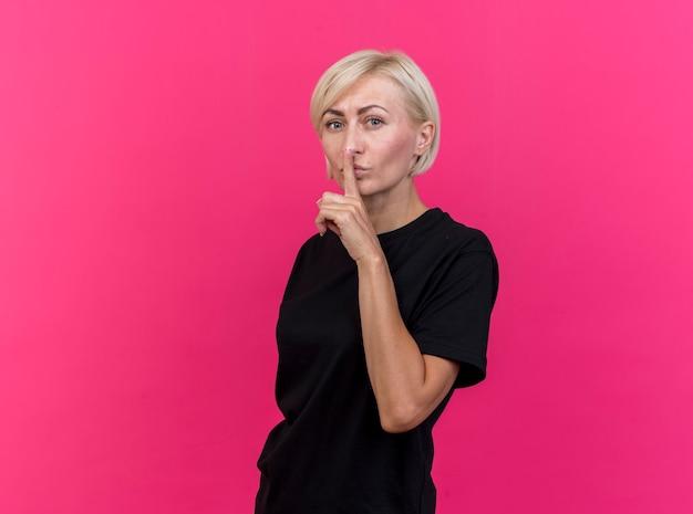 Blonde slavische vrouw van middelbare leeftijd die zich in profielmening bevindt die stiltegebaar doet dat op karmozijnrode muur met exemplaarruimte wordt geïsoleerd