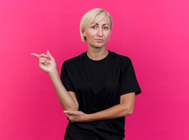 Blonde slavische vrouw van middelbare leeftijd kijken camera hand zetten elleboog wijzend op kant geïsoleerd op karmozijnrode achtergrond met kopie ruimte