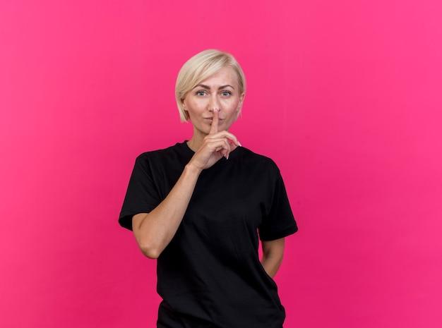 Blonde slavische vrouw van middelbare leeftijd kijken naar camera houden hand achter rug doen stilte gebaar geïsoleerd op karmozijnrode achtergrond met kopie ruimte
