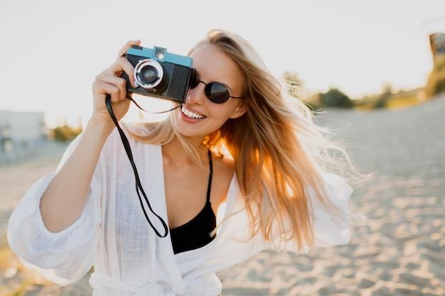 Blonde speelse vrouw die retro camera houdt en pret op warm zonnig strand heeft. zomervakantie en reizen concept. natuurlijke schoonheid, vakantie in azië. trendy zonnebril, witte outfit.