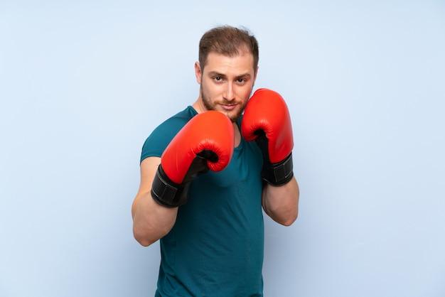 Blonde sport man blauwe muur met bokshandschoenen