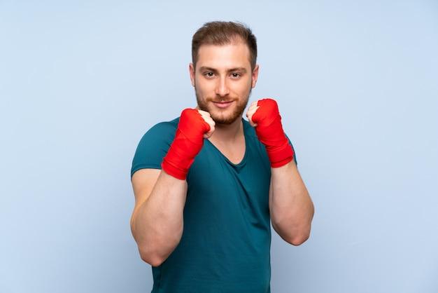 Blonde sport man over blauwe muur in boksen verbanden
