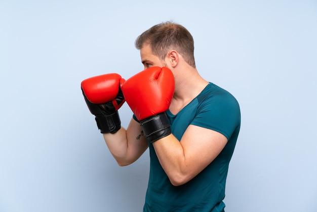 Blonde sport man over blauwe muur met bokshandschoenen