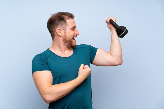 Blonde sport man over blauwe muur met kettlebell