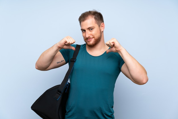 Blonde sport man over blauwe muur trots en zelfvoldaan