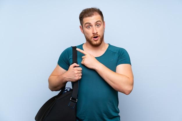 Blonde sport man over blauwe muur verrast en wijzend kant