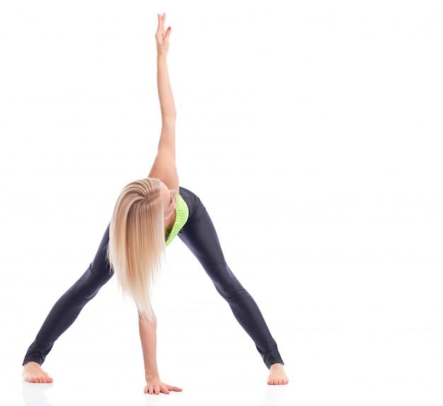 Blonde sportvrouw die geïsoleerde yoga copyspace aan de kant uitvoert