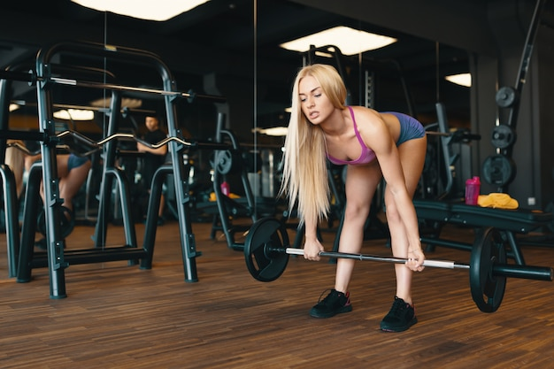 Blonde sportvrouw in mini shorts barbell opheffen op gym training