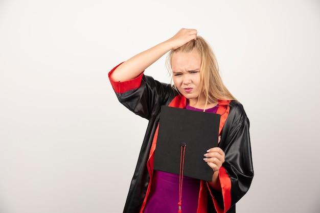 Blonde student die haar pet vasthoudt terwijl hij aan een witte muur denkt.