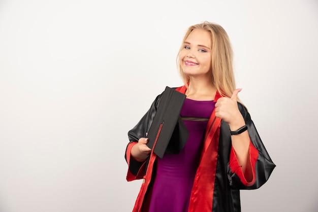 Blonde student houdt haar pet vast en maakt duimen op wit.