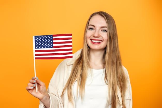 Blonde student meisje houdt een kleine amerikaanse vlag en glimlacht