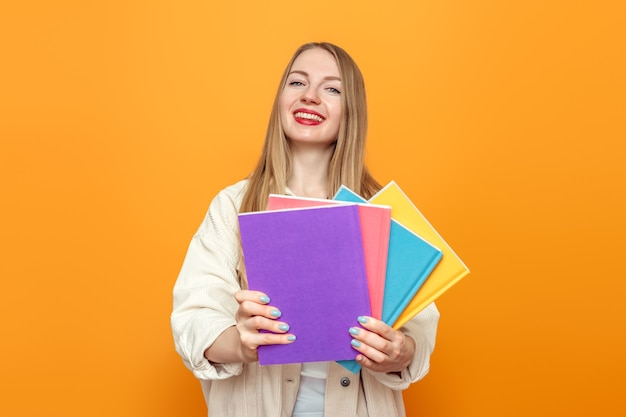 Blonde student meisje in jas houdt vier boeken in veelkleurige omslagen lachend
