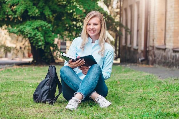 Blonde student meisje lacht en houdt een map en een notebook in haar handen op de universiteit
