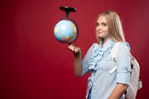 Blonde student vrouw houdt een wereldbol ondersteboven.
