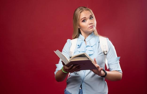 Blonde student vrouw leest een boek en begrijpt.