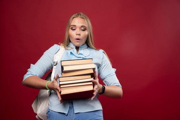 Blonde student vrouw met een stapel boeken en ziet er positief uit.