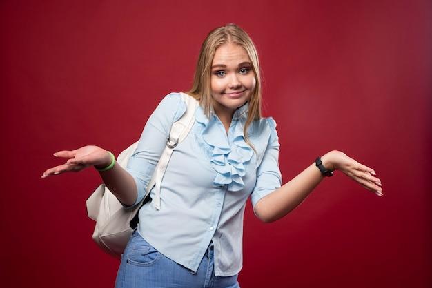 Blonde student vrouw met rugzak kijkt onverschillig.