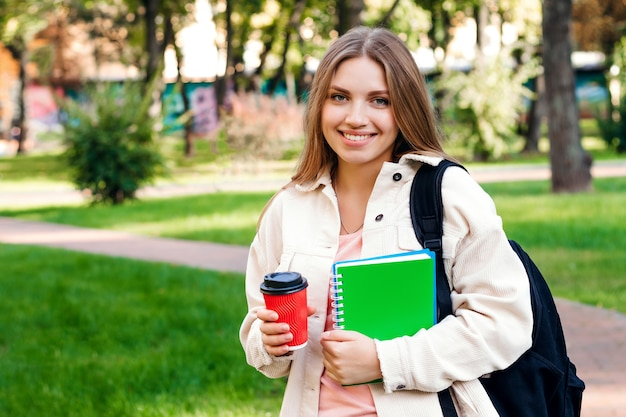 Blonde studente loopt in het park met een laptop en een kopje koffie