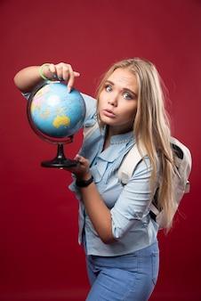 Blonde studentenvrouw houdt een wereldbol vast en kijkt verrast.