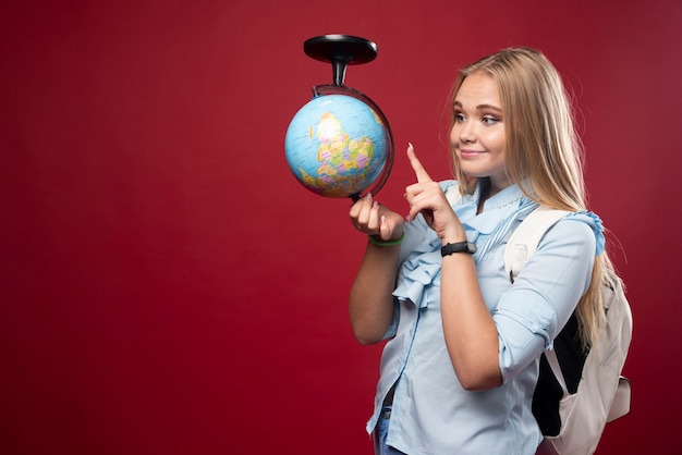 Blonde studentenvrouw houdt een wereldbol vast en wijst een plaats aan.