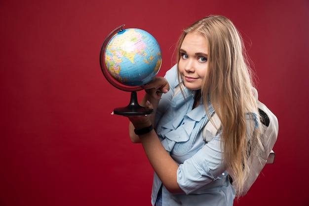 Blonde studentenvrouw houdt een wereldbol vast en ziet er positief uit.
