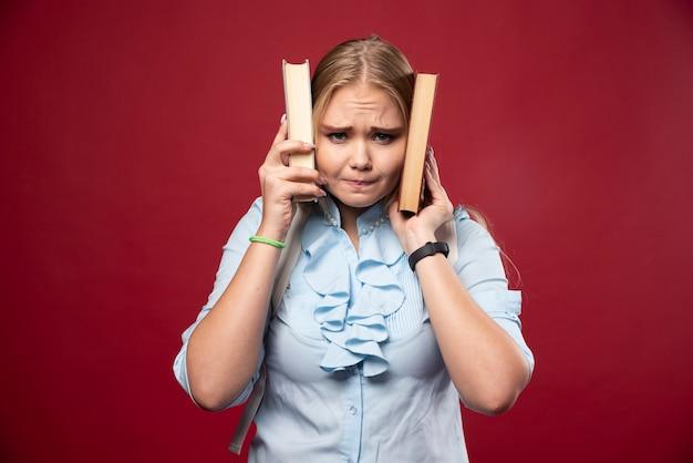 Blonde studentenvrouw houdt haar boeken vast en bedekt haar oren ermee.