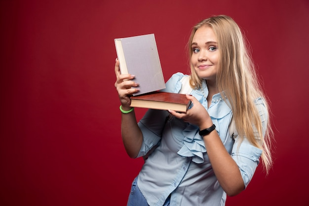 Blonde studentenvrouw houdt haar boeken vast en voelt zich gelukkig.