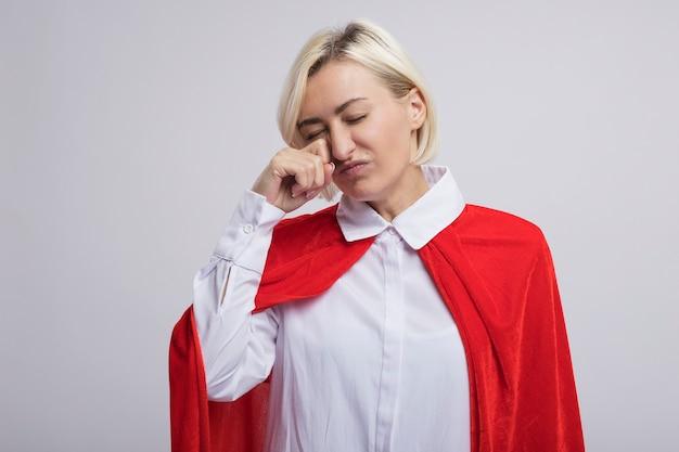 Blonde superheld vrouw van middelbare leeftijd in rode cape die het oog afveegt met de hand met gesloten ogen