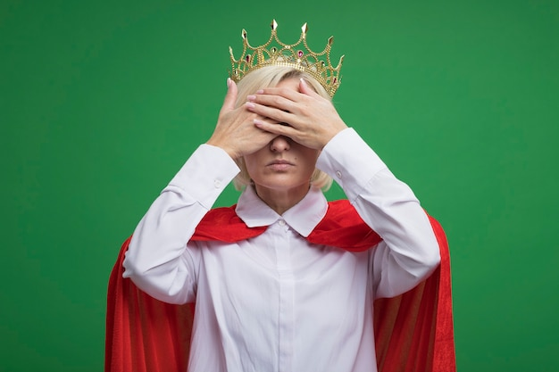 Blonde superheld vrouw van middelbare leeftijd in rode cape met een bril en een kroon die de ogen bedekt met handen